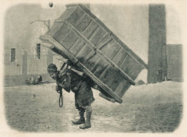Extraordinary photographic postcard of an Armenian porter carrying a ridiculously large wooden box on his back