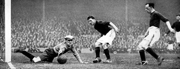 Photograph showing Dixon, the Stoke goalkeeper, attempting to save a shot from one of the Arsenal forwards, during the F.A. Cup Sixth Round match held at Highbury Stadium, 1928. Unfortunately for Dixon, Arsenal emerged victorious from this match