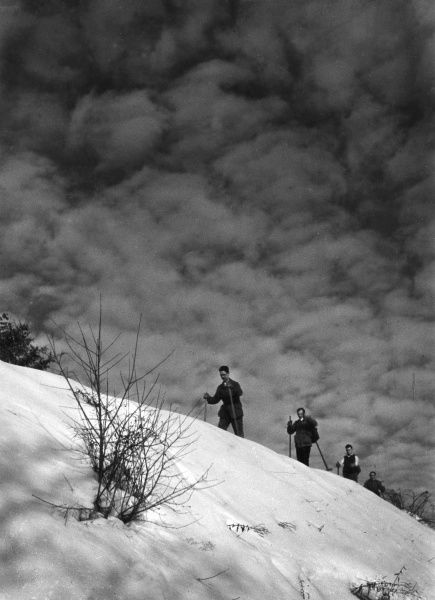 A group of skiers climbing a hill on their skis. Date: 1930s