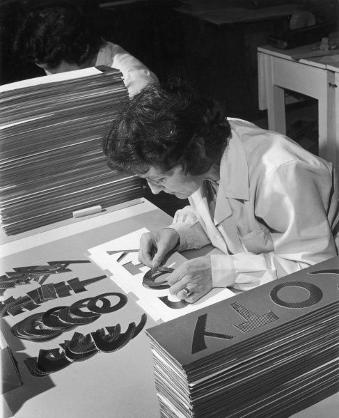 A female factory worker assembles a sign as part of a production line for COTY Beauty House. Photograph by Heinz Zinram