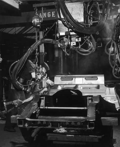 A factory worker assembling the main section of a car undercarriage. Photograph by Heinz Zinram