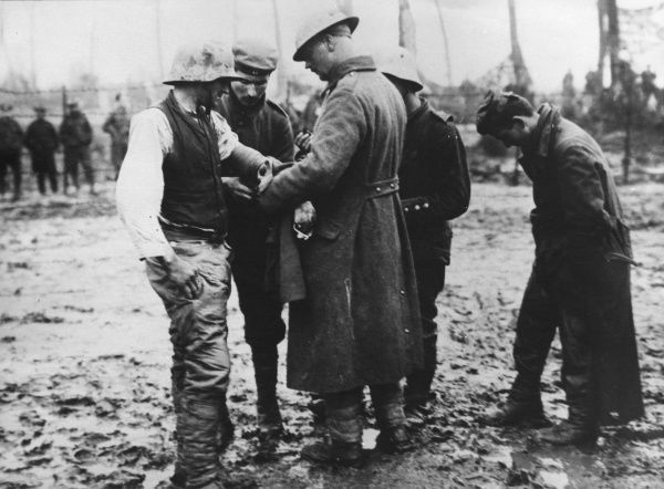 An Allied soldier attending to a wounded German prisoner in a muddy field during the First World War. Date: 1914-1918