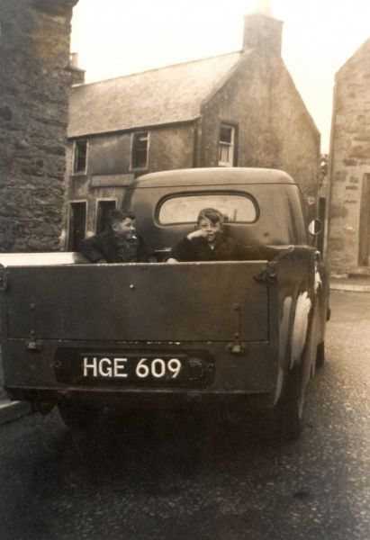 Two young boys sit in the open Austin A40 in Devon