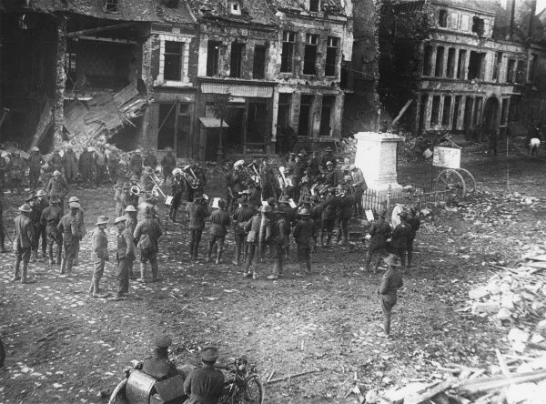 An Australian band playing in the town square at Bapaume, northern France, during the First World War, with ruined buildings in the background and debris on the ground. Date: circa 1917