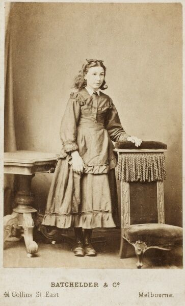 A rare cabinet photograph from Collins Street, Melbourne, Australia depicting a young lady in fine dress in a studio setting