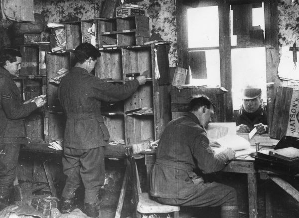 Scene inside the Australian Field Post Office at Henencourt, northern France, during the First World War, showing men sorting the post into pigeonholes. Date: March 1918