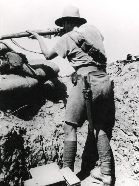 An Australian soldier taking aim with his rifle near Gaza during the First World War. Date: circa 1917