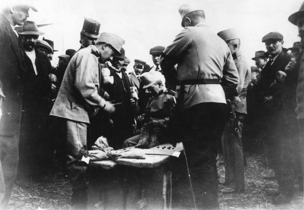 Newly recruited members of the Austrian army receive their first pay on mobilisation at the start of the First World War. An official takes coins out of a canvas bag. Date: 1914