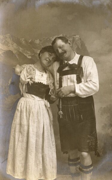 Jolly Tyrol Austrian Couple in traditional attire standing in front of a studio mountain backdrop - slightly sickly... Date: circa 1910s