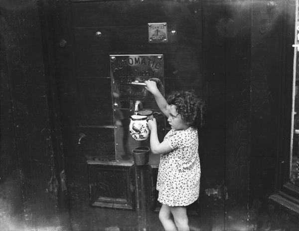 A little girl demonstrates how easy it is to fill up a jug with milk from an automatic milk machine!