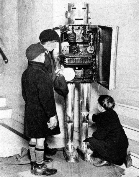 A physiological robot at the Schoolboys' Own Exhibition in London, 1929. Designed to show how organs of the body work, here three young visitors take great interest in its insides. Date: 1929