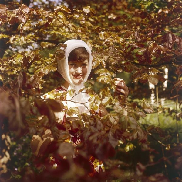 A coy model hides hehind the autumn leaves. Date: 1960s