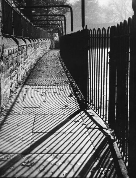 Autumn shadows from railings across a lonely walled walkway