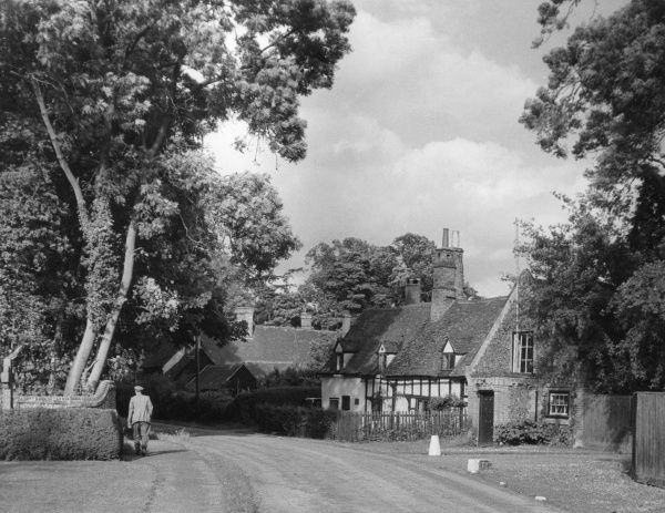 Ayot St. Lawrence, Hertfordshire, England - view from the village green, where a row of Medieval cottages leads to the tiny post office and inn. Date: 1950s