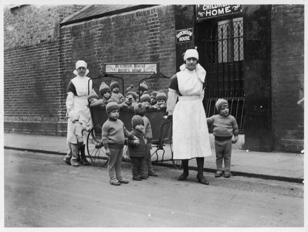 Nurses with a pramful of small children from Hutchison House Babies Home. Date: early 1930s