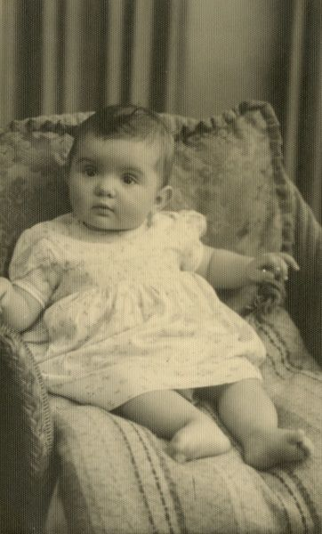 A baby, around six months old, sitting up in a chair on some comfy cushions. Date: November 1954
