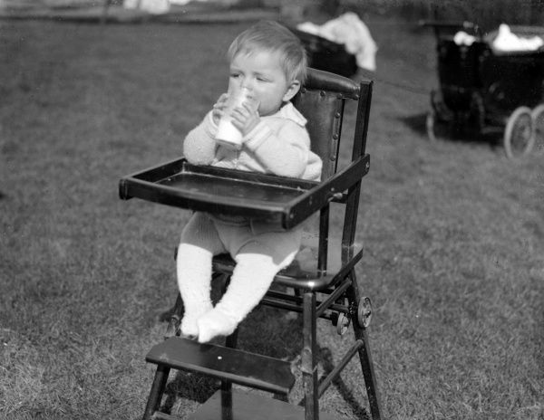 An Adoption Society baby drinking milk in a high chair in the open air, England. Date: early 1930s