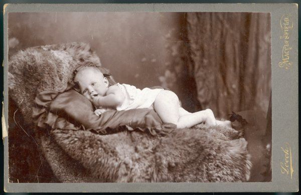 Terence Hope Davenport, age ten months, lying on a fur rug in the photographer's studio