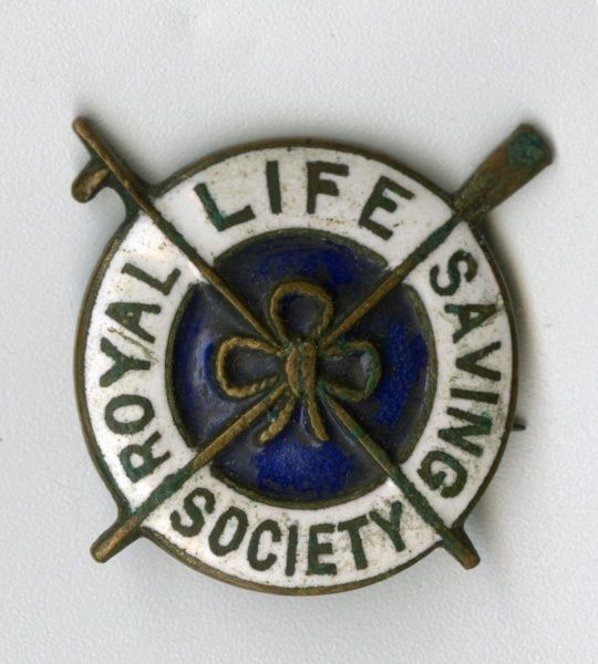 Badge of the Royal Life Saving Society, featuring a lifebelt design. Date: early 20th century