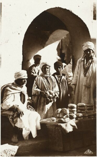 A Baker selling his wares from a low streetside crate-mounted stall, Morocco