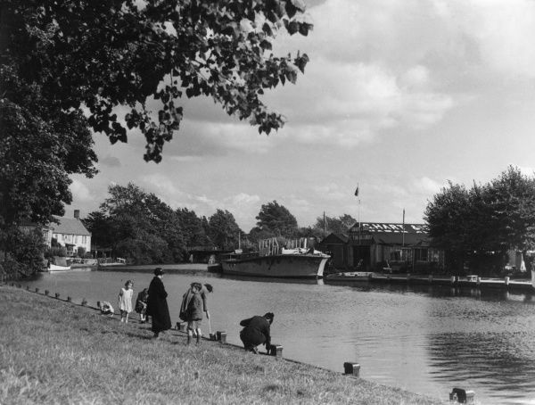 Mothers and children on the banks of the River Yare, flowing placidly through the picturesque little village of Thorpe-next-Norwich, Norfolk, England. Date: 1930s