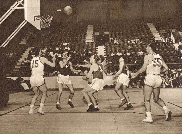 In this sparsely-attended basketball match at Harringay Arena, the American team (in white) beat the Swiss team. Date: 1948