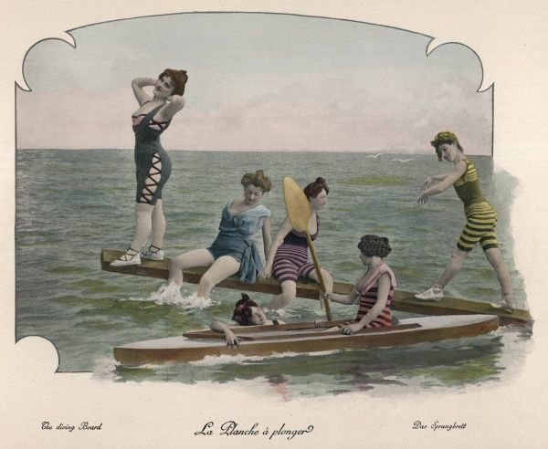 Six bathing beauties, four on a springboard, two with a canoe