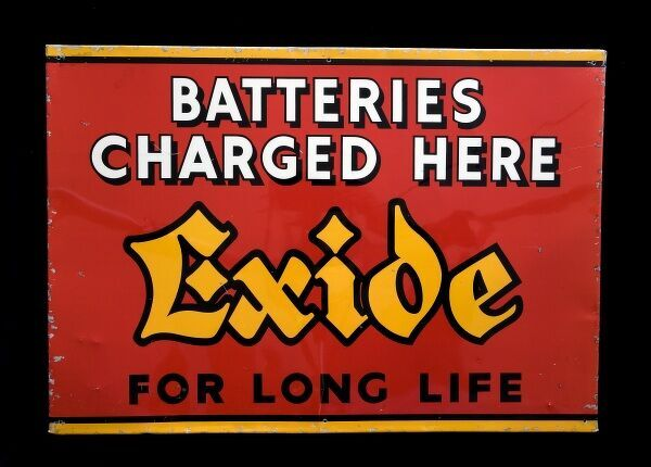 A tin/alloy sign advertising Exide batteries, mentioning that batteries can be 'Charged Here'. *EDITORIAL USE ONLY*