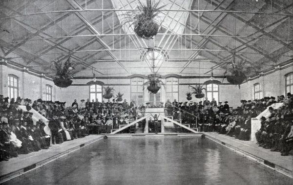 Interior view of the opening of the new women's swimming bath at Battersea, south-west London. Guests at the ceremony are seated around the pool while a swimmers prepares to dive into the water. Date: 1904