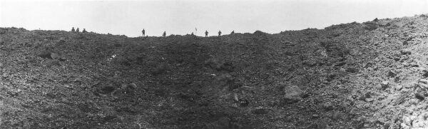 Soldiers on the rim of a huge mine crater blown up on the morning of the battle of Messines Ridge on the British Front in France during World War I in June 1917