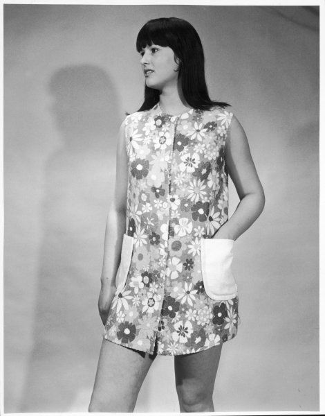 A short, sleeveless, button front beach robe in a bold floral print and with large, plain patch pockets