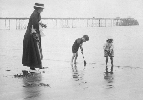 A little boy and girl play with their spades on the beach, while their mother, looking rather cold, holds their coats and watches over them