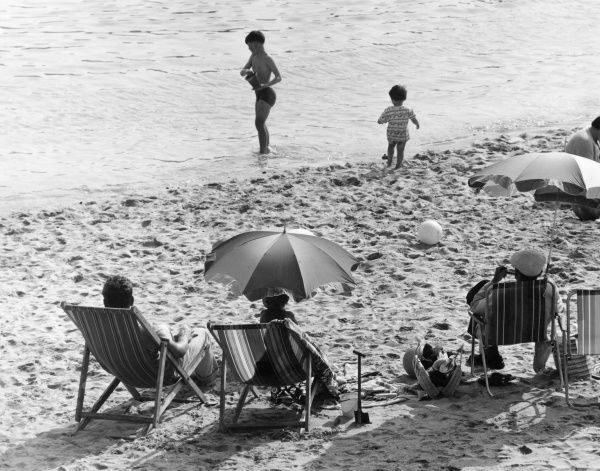 Adults sit under umbrellas on deckchairs on the beach, while children play in the sand and sea. Date: 1960s