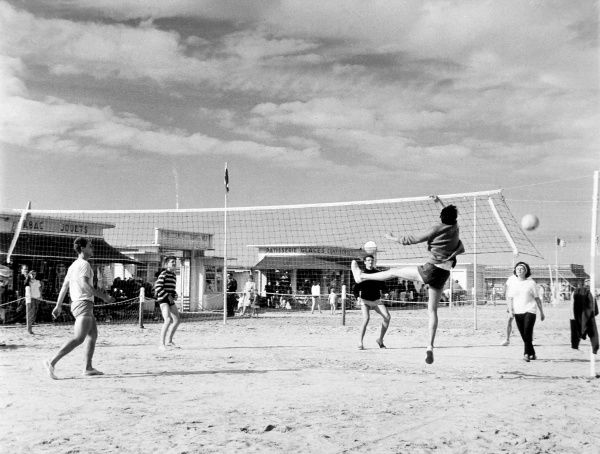A game of beach volleyball in France. Date: 1950s
