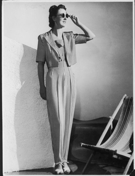 BEACH WEAR: two-piece costume for wearing over a swimsuit composed of high-waisted trousers hung from braces & tapered at the ankle with a draw-string & a bolero