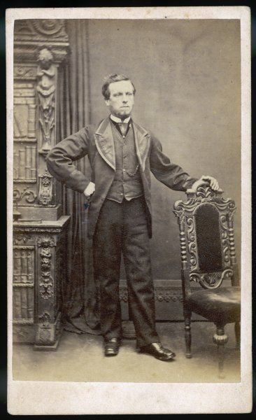 A bearded man with one hand on his hip wears collarless waistcoat & jacket with braid on the cuffs, broad silk faced lapels & with the fronts sloping away from above waist level
