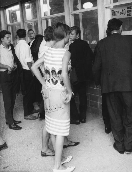 A girl in East Germany wears a dress with images of The Beatles