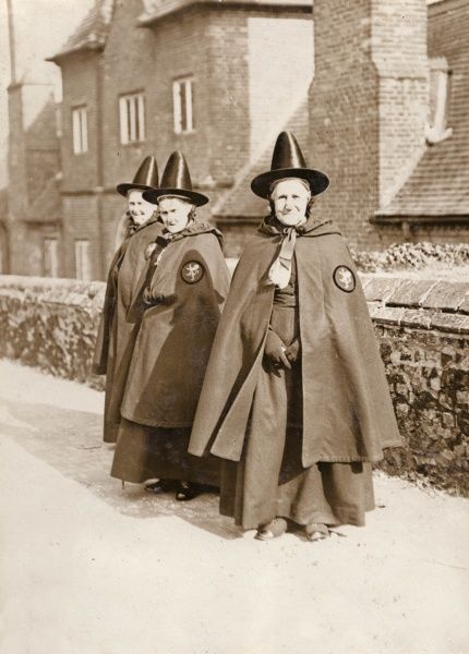 Three bedeswomen of Castle Rising, near Sandringham in Norfolk. When these elderly women enter the almshouses (known collectively as Trinity Hospital) they are required to wear an old Welsh costume, including a distinctive red cloak and black pointed hat