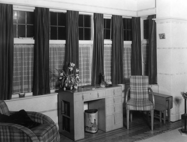 A modern desk and waste paper bin have certainly cheered up this rather large Edwardian bay window and made a small bedroom office area. Date: 1930s