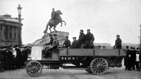 Photograph captioned 'The new power and the old potenate; Benzine motor adopted for use in the Russian army passing Peter the Great's statue&#39
