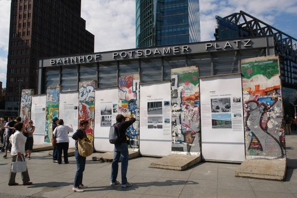 Tourists view some remains of the Berlin Wall, on display in the Potsdamer Platz, Berlin, Germany