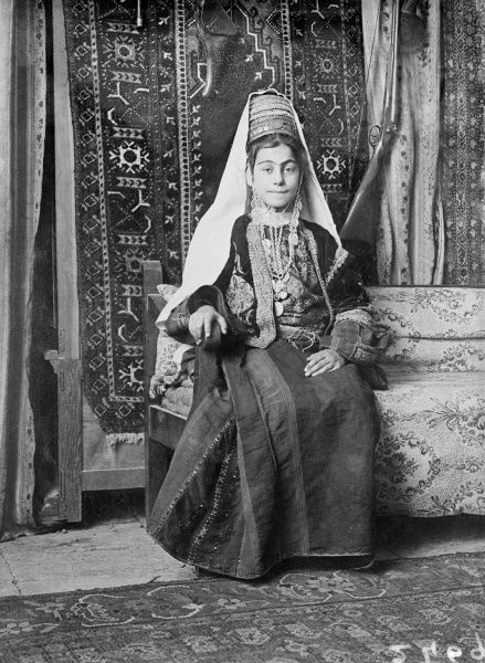 A young bride wearing her dowry and traditional wedding dress, Bethlehem, Jerusalem. Date: early 1930s