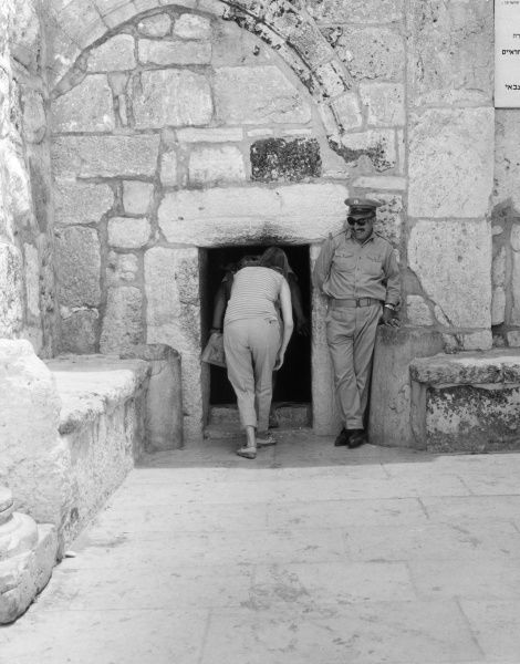 A security guard smiles as a couple of tourists enter a historic building in Bethlehem, Israel. Date: late 1960s