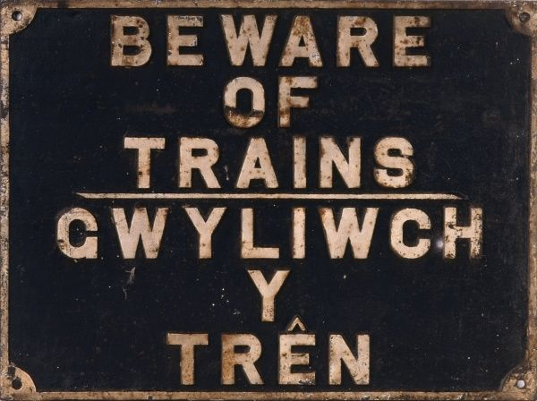 A metal sign in English and Welsh stating - 'Beware of Trains' - likely to have been positioned at a footpath crossing or at a station