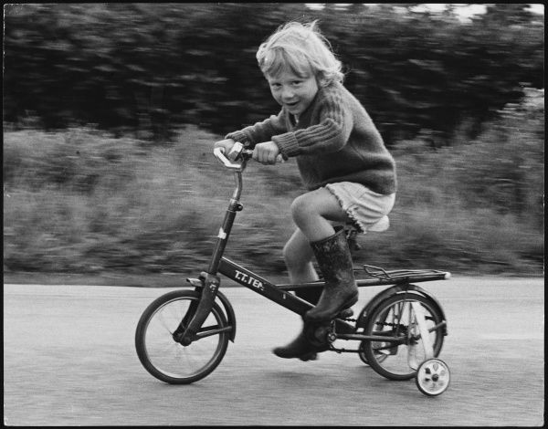 A child riding a bicycle with stabilisers on it