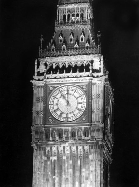 The clock face Big Ben, Houses of Parliament, Westminster, central London, floodlit at night for dramatic effect. Date: 1930s