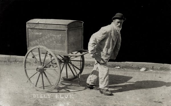 Billy Blue, an inmate of the Holsworthy Union workhouse, Devon, pulling a handcart on which is a large chest bearing the workhouse's name. Billy is wearing the typical workhouse uniform of jacket, trousers, waistcoat and bowler or billycock hat