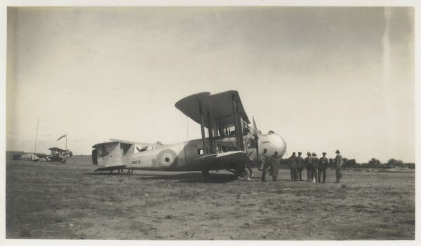 A biplane bomber converted for passenger use, somewhere in the Middle East. A group of passengers can be seen standing in front of the plane