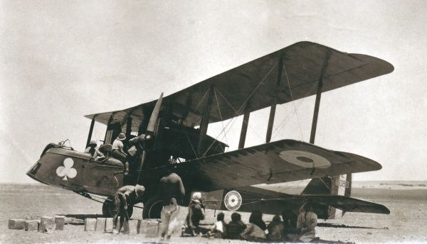 A biplane bomber in the desert, with crew and arabs resting in the shade of the wings, somewhere in Iraq. Cans of fuel can be seen spread out on the ground