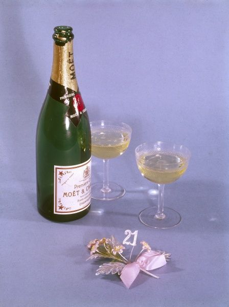 A bottle of champagne and two glasses, ready to drink a 21st birthday toast! Date: 1966